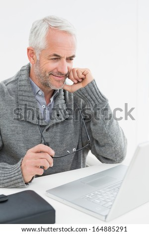Smiling mature man using laptop at desk against white background