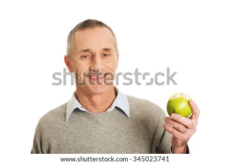 Smiling mature man with an apple. - stock photo