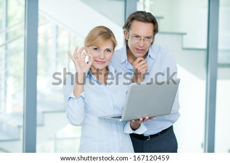 Smiling mature manager standing upright next to of his business parnter - ok sign, computer, glass office - stock photo
