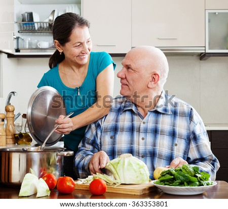 Smiling mature married couple cooking vegetarian lunch together in domestic kitchen - stock photo