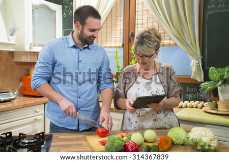 Smiling mature mother and her adult son making healthy salad in the kitchen. Young man is cutting tomato while mother is showing him a recipe on digital tablet. - stock photo