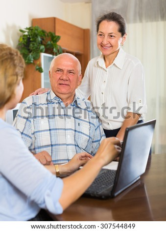 Smiling mature people discussing for agent or employee of  company at home - stock photo