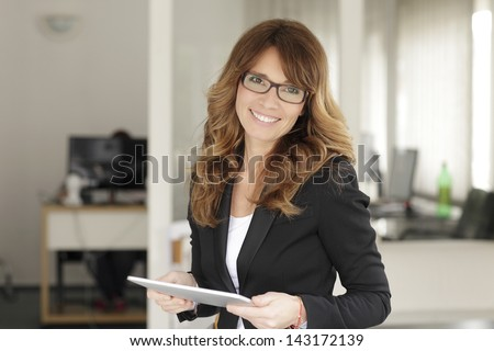 Smiling mature professional businesswoman standing in office. Holding a digital tablet . Shallow focus. - stock photo