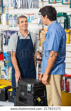 Smiling mature salesman showing tool case to customer in hardware store