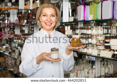 Smiling mature saleswoman posing with delicious honey  and marmalades in jars