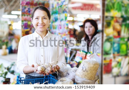 Smiling mature woman buys garlic for planting on the market - stock photo