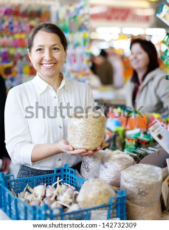 Smiling mature woman buys the seeds in bag on the market - stock photo
