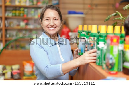 Smiling mature woman chooses agricultural chemistry at garden store - stock photo