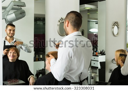 Smiling mature woman cutting hair in the barbershop