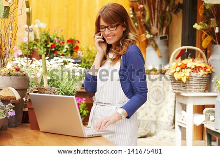 Smiling Mature Woman Florist Small Business Flower Shop Owner.  She is using her telephone and laptop to take orders for her store. Shallow Focus. - stock photo