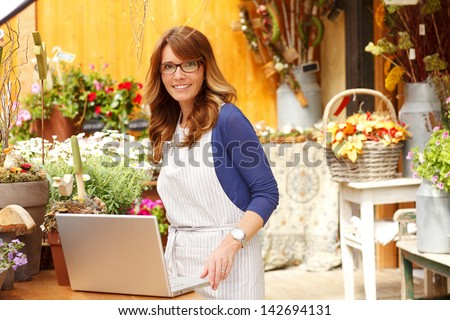 Smiling Mature Woman Florist Small Business Flower Shop Owner.  She is using laptop to take orders for her store. Shallow Focus. - stock photo