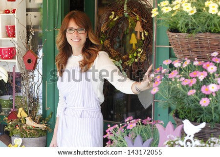 Smiling Mature Woman Florist Small Business Flower Shop Owner standing in front of her shop. Shallow Focus. - stock photo
