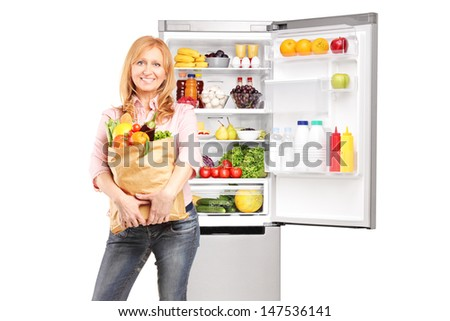 Smiling mature woman holding a paper bag full of groceries in front of refrigerator, isolated on white background - stock photo
