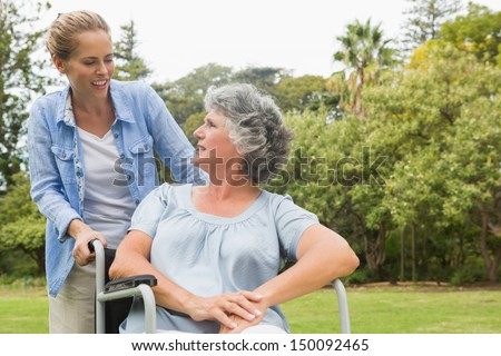 Smiling mature woman in wheelchair talking with daughter on sunny day in park
