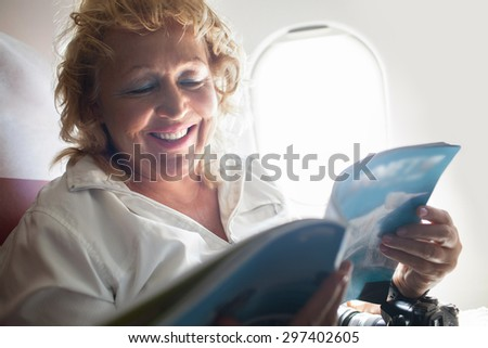 Smiling mature woman is sitting by window on a plane with magazine in hands. - stock photo