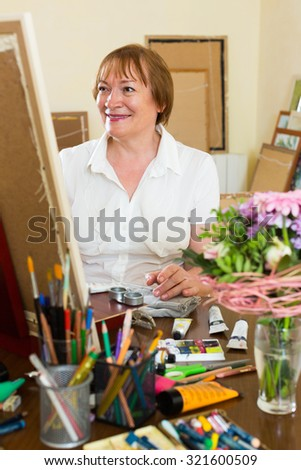 Smiling mature woman painting for fun with paints at home studio - stock photo