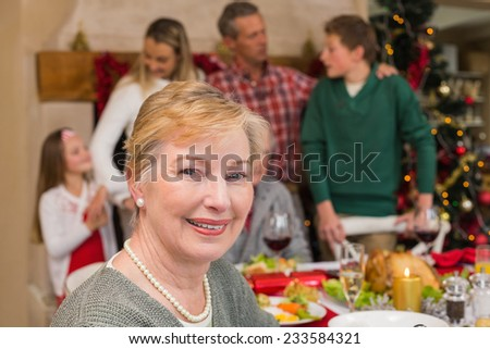 Smiling mature woman posing in front of her family at home in the living room - stock photo