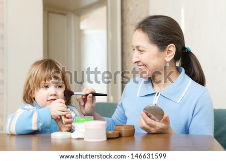 Smiling mature woman  putting facepowder on her face of little girl with brush