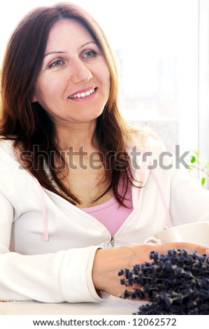 Smiling mature woman relaxing at home holding a cup - stock photo