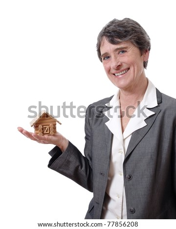 smiling mature woman showing a tiny chalet in her hand isolated on white background - stock photo