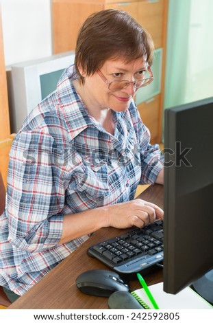 Smiling mature woman sitting in front of PC and using keyboard - stock photo