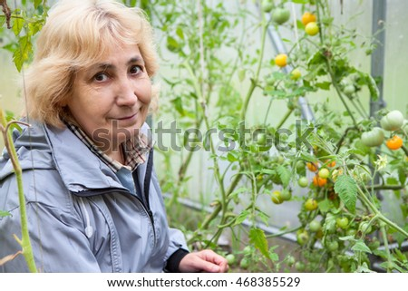 Smiling mature woman sitting in greenhouse with growing tomatoes