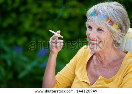 smiling mature woman sitting in the garden smoking - stock photo