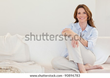 Smiling mature woman sitting on her sofa - stock photo