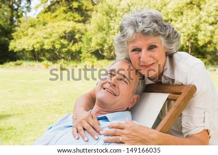 Smiling mature woman standing behind her husband on deck chair and looking at camera - stock photo