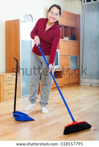 Smiling mature woman sweeping the floor