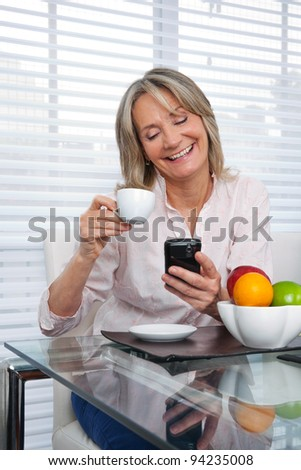Smiling mature woman using cell phone while having tea - stock photo