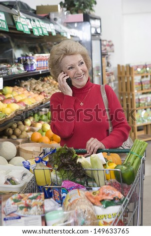 Smiling mature woman using cellphone while doing grocery shopping in supermarket