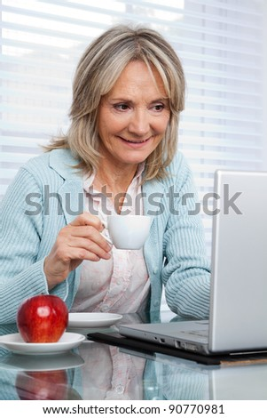 Smiling mature woman working on laptop while having cup of tea - stock photo