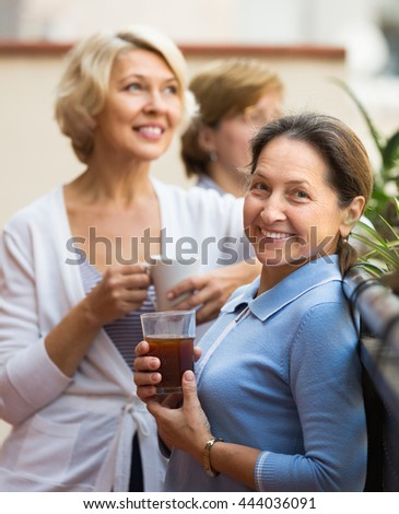 Smiling mature women drinking tea with cookies at balcony. Focus on brunette