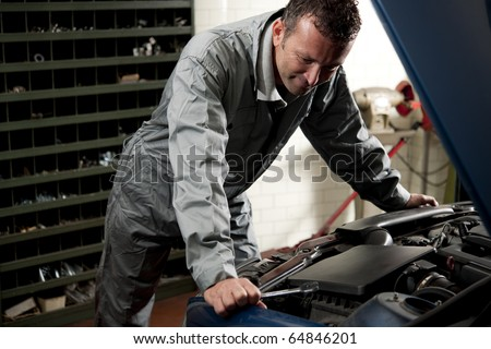 Smiling mechanic controlling car engine