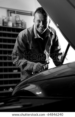Smiling mechanic controlling car engine - stock photo