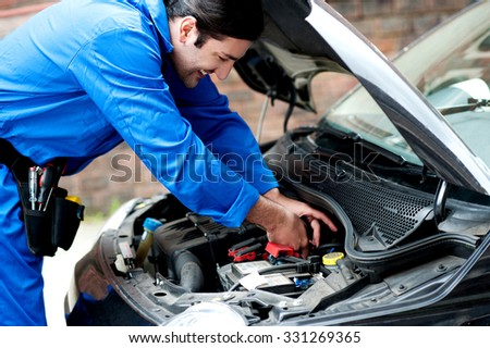 Smiling mechanic doing a maintenance check - stock photo
