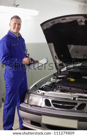 Smiling mechanic holding a clipboard and a pen in a garage