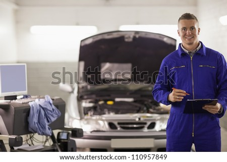 Smiling mechanic holding a clipboard next to a car in a garage