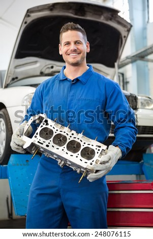 Smiling mechanic holding an engine at the repair garage - stock photo
