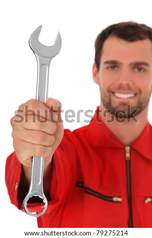Smiling mechanic holding wrench. Selective focus on hand in foreground. All on white background.