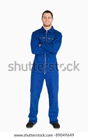 Smiling mechanic in boiler suit against a white background - stock photo