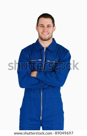 Smiling mechanic in boiler suit with folded arms against a white background - stock photo