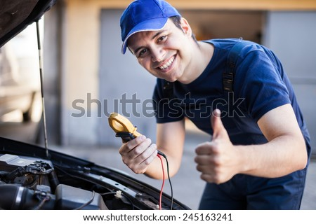 Smiling mechanic troubleshooting a car engine - stock photo