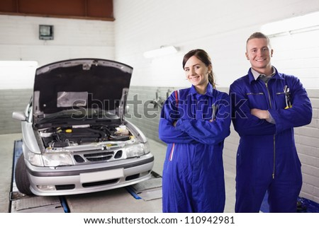 Smiling mechanics with arms crossed next to a car in a garage - stock photo