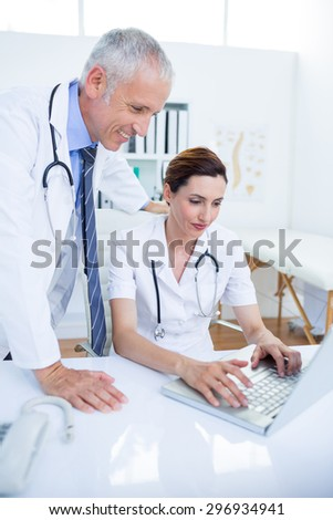 Smiling medical colleagues working with laptop in the hospital
