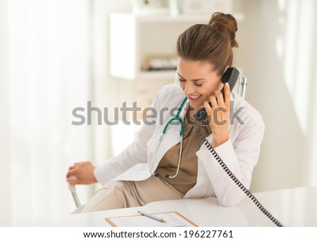Smiling medical doctor woman talking phone - stock photo