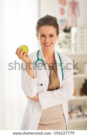 Smiling medical doctor woman with apple - stock photo
