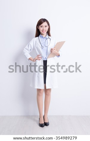 Smiling medical doctor woman with stethoscope and clipboard. with white wall background. asian - stock photo