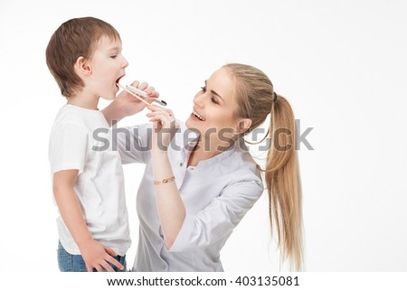 Smiling medical doctor woman with stethoscope.  The doctor looks at the baby boy's throat swab and a flashlight  Isolated over white background. - stock photo